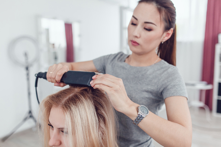 Hairdresser-stylist does the styling to the girl, using hair styling. Corrugated on the hair. Stock Photo