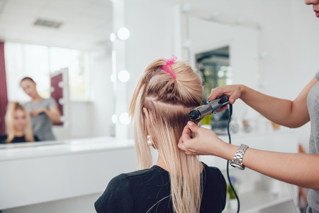 Hair stylist makes a curls for a girl, using hair styling. Hairdresser at work.