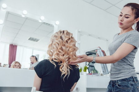 makes: Hair stylist makes a curls for a girl, using hair styling. Hairdresser at work.