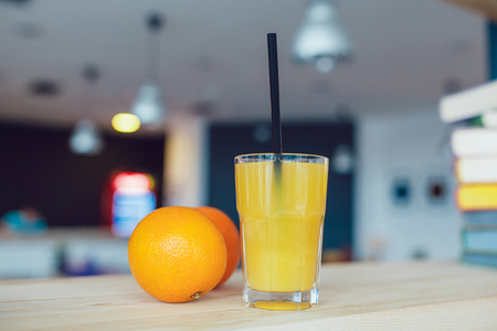 Glass of orange juice with fruits and cocktail straws on a table.