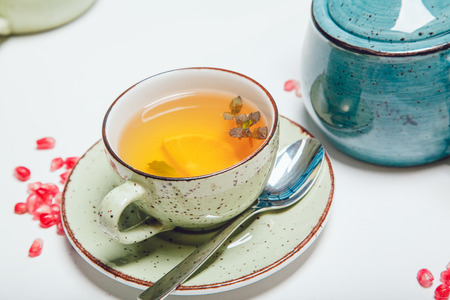 Tea in cup with leaf mint and lemon on white table.