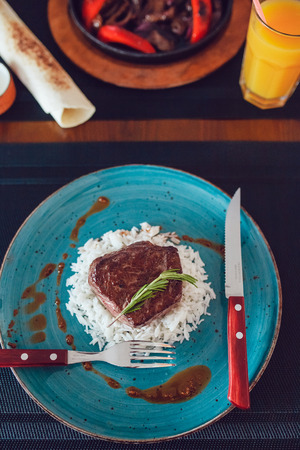 Delicious beef grilled whith rice on the table with a knife and fork.
