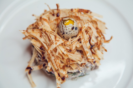 recipe decorated: Salad in the form of a nest and decorated with quail eggs.