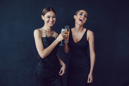 rumour: Attractive women in cocktail dresses are holding glasses of champagne, talking and smiling.