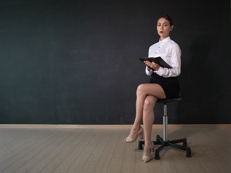 Business woman sitides on a chair and holds documents. Imagens