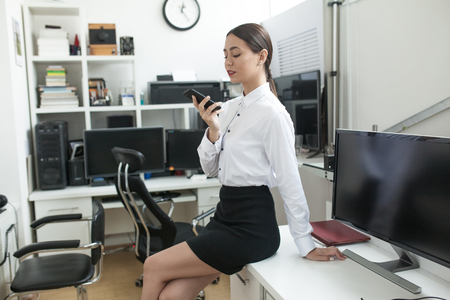 Business woman sitting in office and using smartphone. Stock Photo
