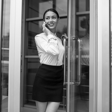 Business woman exits from business center and speaks by phone. Stock Photo