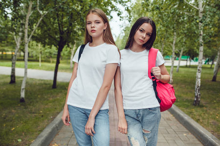 Girls in white T-shirts walking in the park. Mock up.