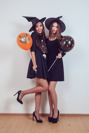 Women in witch halloween costumes standing with balloons on white background.