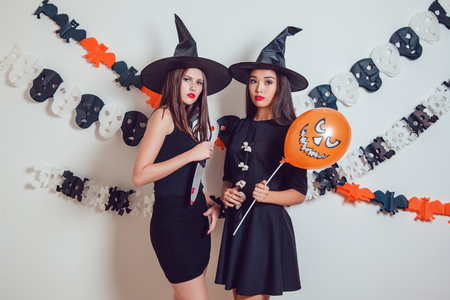 Women in witch halloween costumes standing with a knife and balloons. Stock Photo