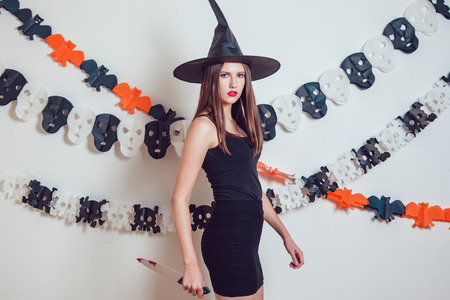 Woman in a witch costume with a knife in her hands. Halloween. Stock Photo