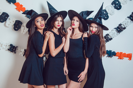 Women in witch halloween costumes standing on white background.