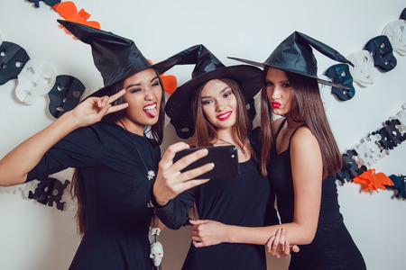 Women in witch halloween costumes standing and make selfie on white background.