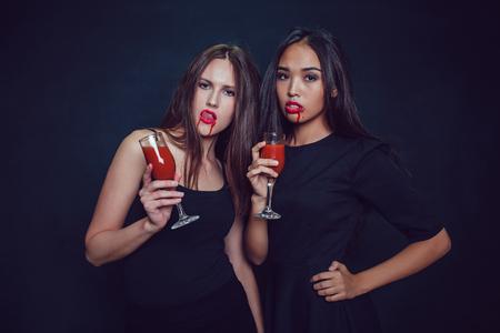 Des filles attirantes à l'image des vampires tiennent des verres de sang. Halloween. Banque d'images - 87403445