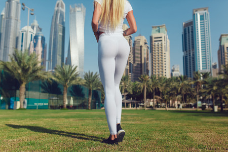 Legs of a sexy girl in white leggings. Mock-up. Outdoor.