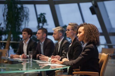 A group of business people sit at a table in a line and are discussing.