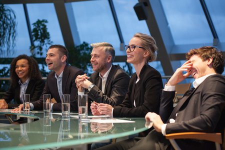 A group of business people sitting at a table discussing and laughing. Stock Photo