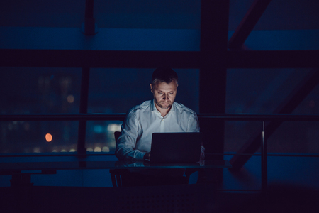 Businessman working on laptop in night office. Imagens - 90927840