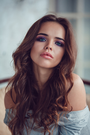 Portrait of a sexy woman with makeup and curls.