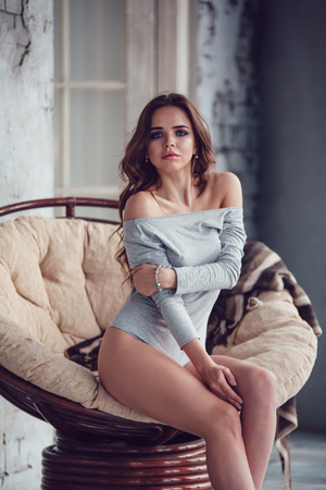 Sexy woman dressed in gray bodysuit sitting in an armchair.