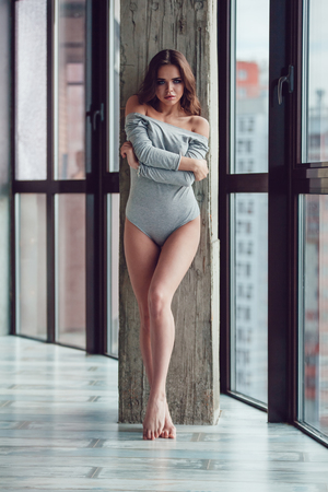 Sexy woman in gray bodysuit stands near the window.