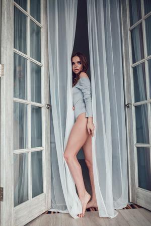 Sexy woman in gray bodysuit is standing in the open door.