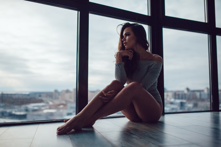 Sexy woman in gray bodysuit sits on the floor near the panoramic window. Stock Photo - 91674851