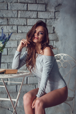 Attractive woman in gray bodysuit sitting at a table with flowers. Stock Photo