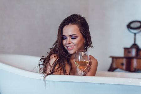 Beautiful sexy woman relaxed in the bath with a glass of wine. Standard-Bild