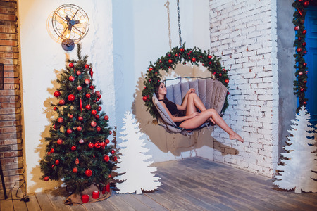 Woman in beautiful underwear sits in a hanging chair near Christmas tree. New year. Stock Photo