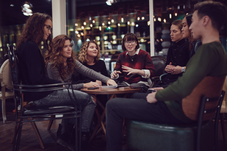 Group of positive teenagers spend time in cafe.