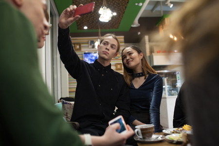 Group of positive teenagers make selfies and spending time in a cafe. 스톡 콘텐츠