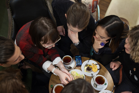 Group of positive teens use a smartphone and spend time in a cafe.