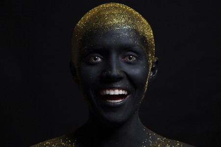 Portrait of a beautiful woman with creative body art glowing make up. Face is colored with black paint. Stock Photo