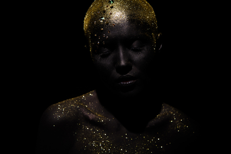 Portrait of a beautiful woman with creative body art glowing make up. Face is colored with black paint. Stok Fotoğraf