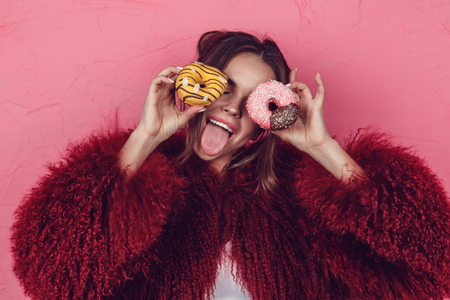 Girl in a bright fur coat with donuts in hands posing on a pink background.