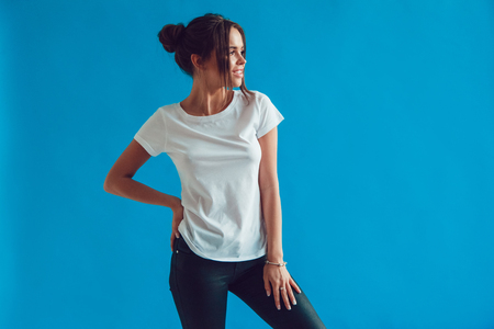Attractive woman in a white t-shirt stands on a blue background. Mock-up. Stok Fotoğraf