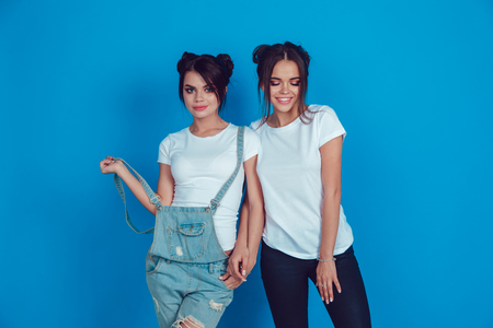 Attractive women in a white t-shirts stands on a blue background. Mock-up. Imagens - 94434596