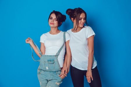 Attractive women in a white t-shirts stands on a blue background. Mock-up.