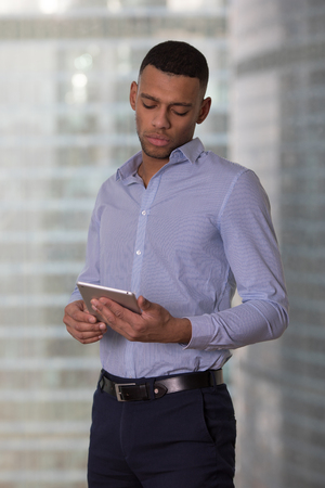Businessman with a tablet in his hands is standing near the window in the office. Stock Photo