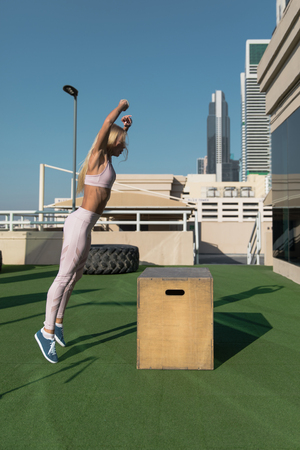 Fit young woman doing box jumping. Stock Photo