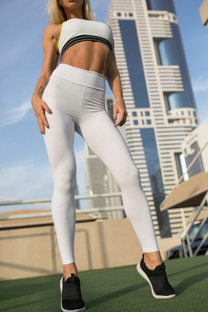 Legs of a sexy girl in white leggings. Mock-up. Outdoor gym.