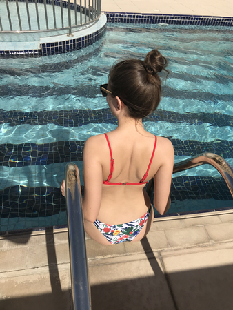 Back view of girl sitting near pool.