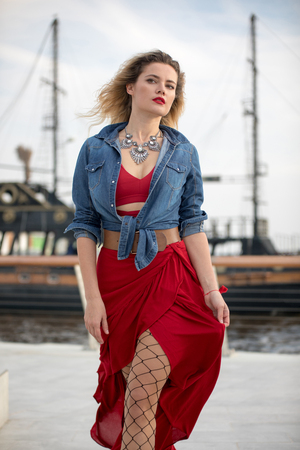 Beautiful woman in a red dress on a ship background.