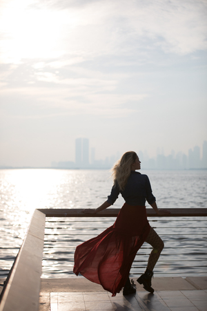 Beautiful woman in red dress on the background of the sea. 写真素材