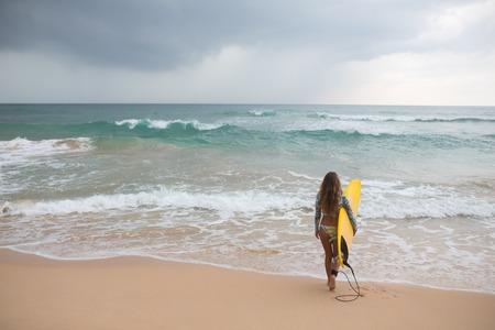 Woman surfer looking at the ocean with a surfboard in his hands.