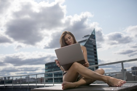 Young woman in a white top and panties sitting on the roof and using laptop.