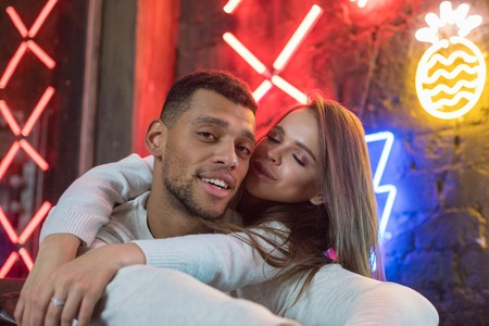 Happy multiracial couple sits embracing on the background of neon lamps.