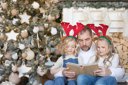 Dad reads daughters a book near the Christmas tree. Reklamní fotografie