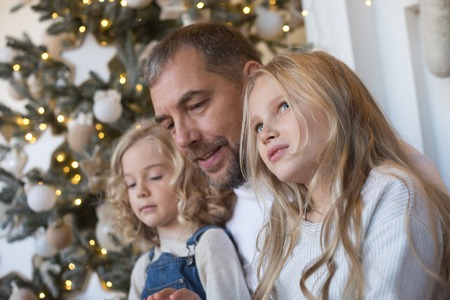 Dad is sitting with two daughters near the Christmas tree. Reklamní fotografie